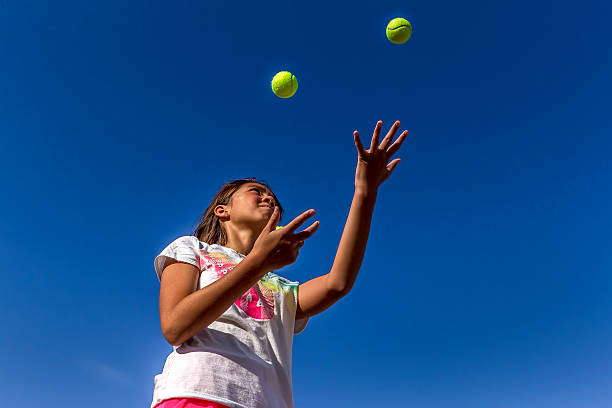 Looking up at girl juggling. stock photo