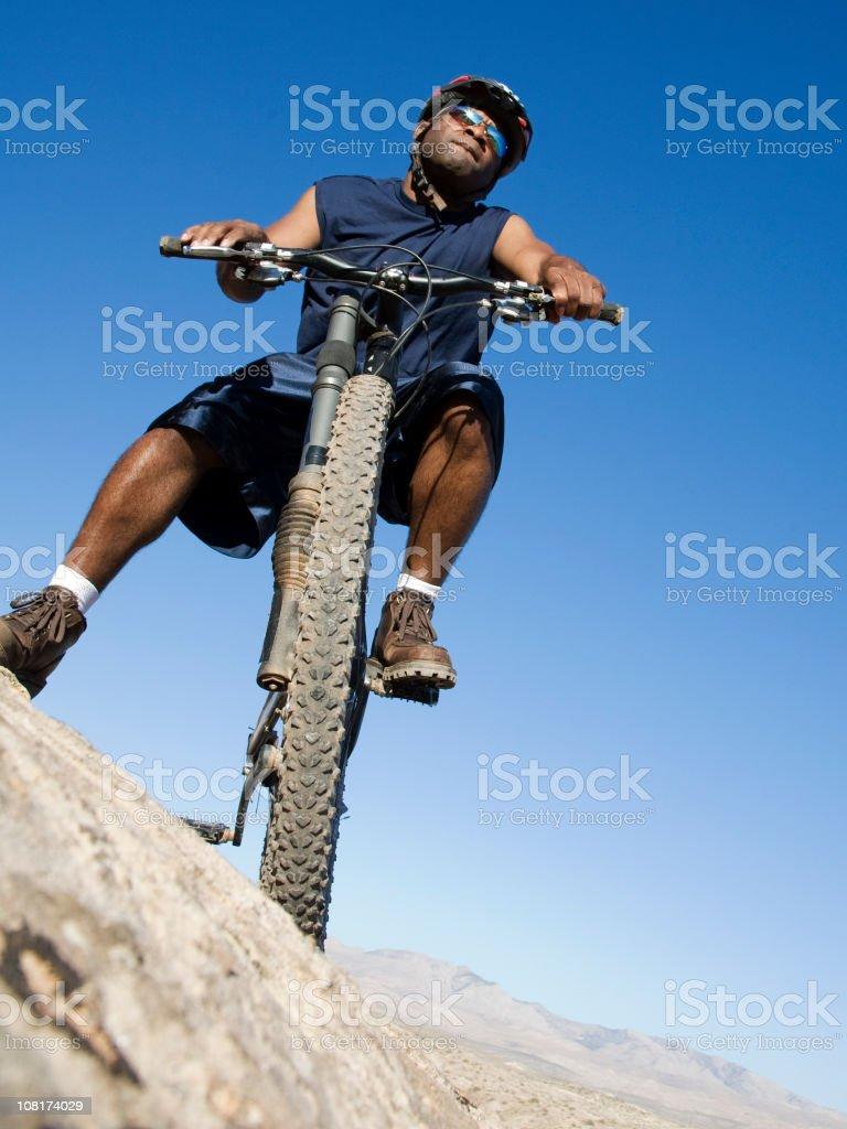 Looking Up at Man Sitting on Mountain Bike royalty-free stock photo