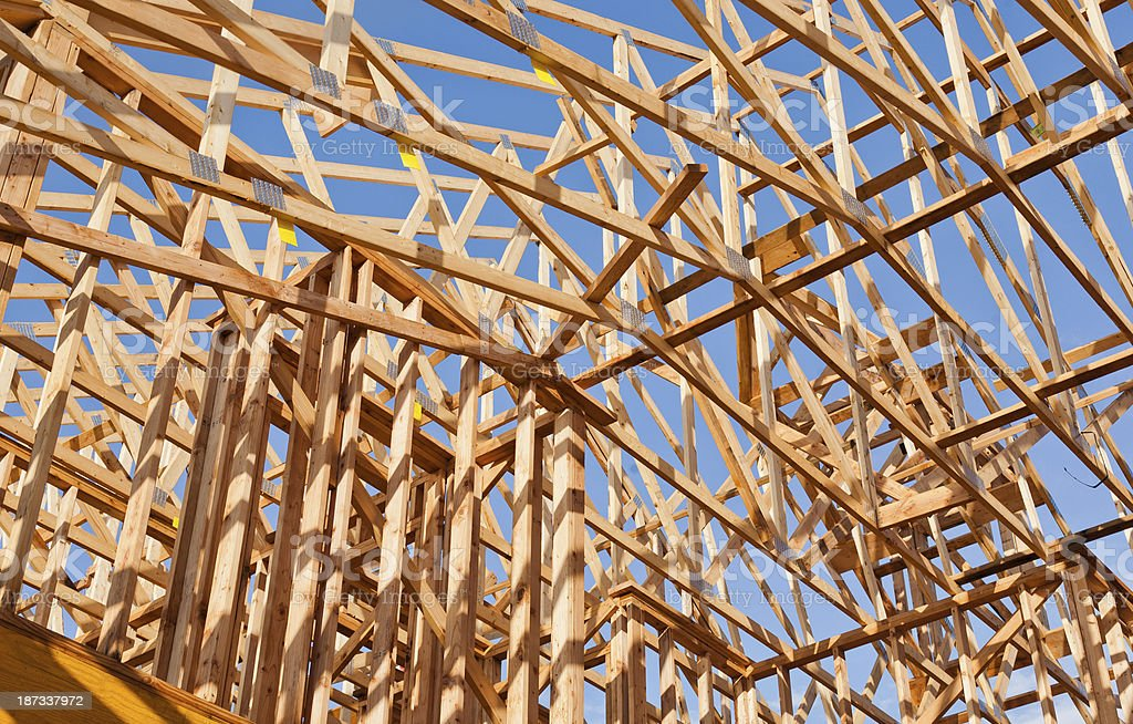 looking up at rows of wood roof trusses royaltyfree stock photo