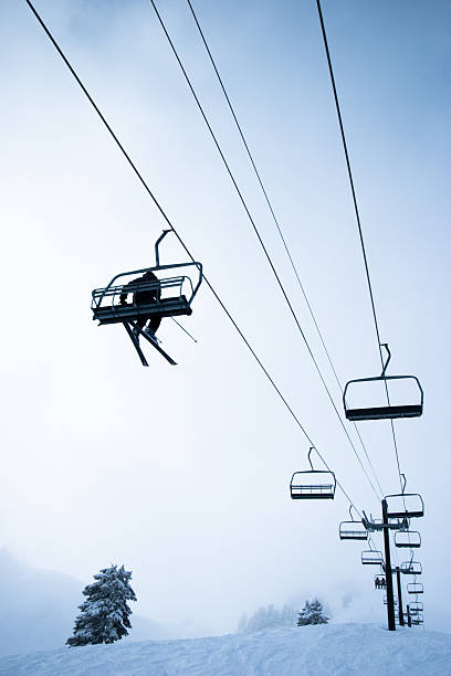 Looking Up at Skier Riding Ski Lift on Mountain stock photo