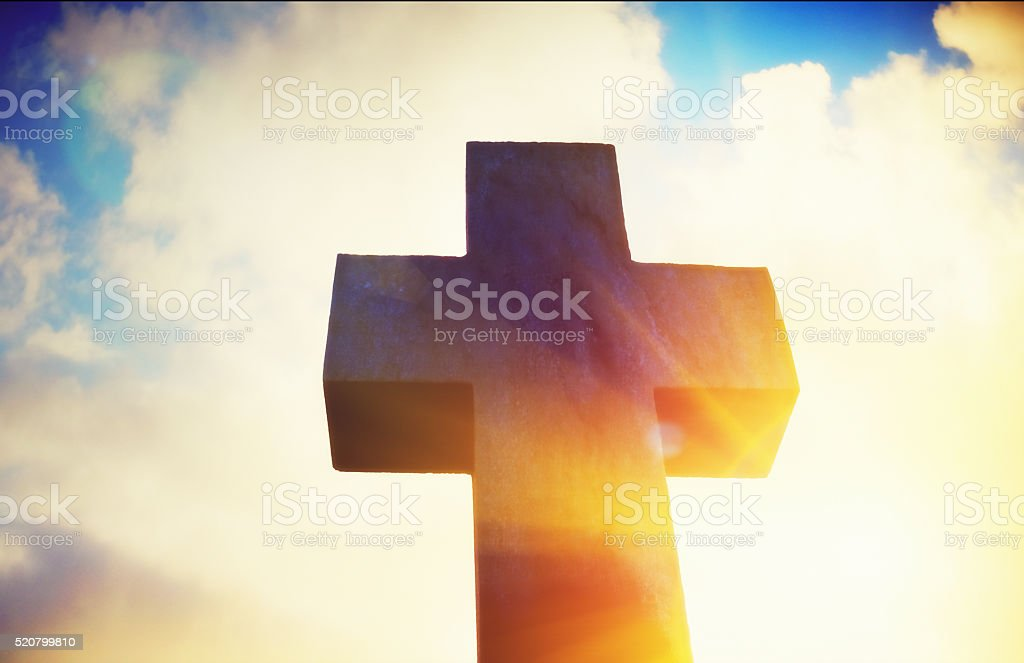 Looking up at stone cross against clouds lit by sun stock photo