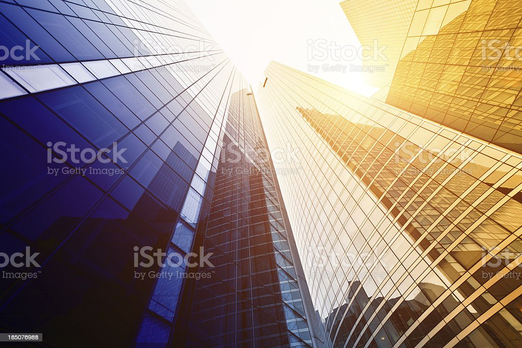 Looking up at tall buildings with sun shining down stock photo