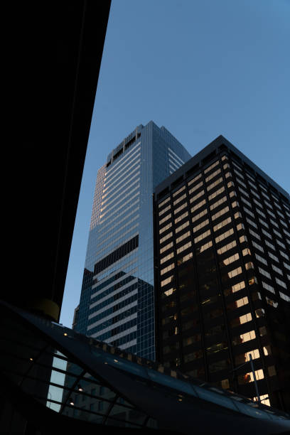 Looking up at tall office buildings at dusk stock photo