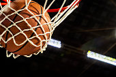 istock Looking up at the bottom of a basketball falling through the net with arena lights in the background 1135431819