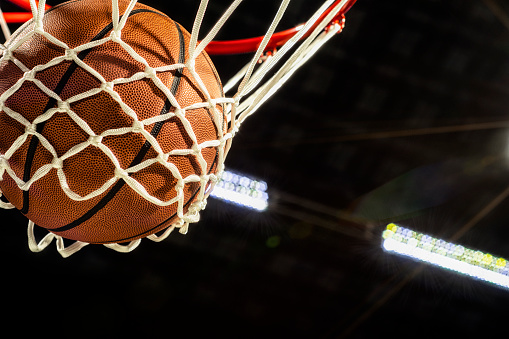 A close-up view looking up at an orange basketball falling through the rim and a white nylon net with the arena lights and lens flare in the background.