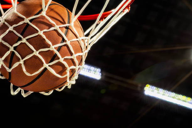 looking up at the bottom of a basketball falling through the net with arena lights in the background - basket foto e immagini stock