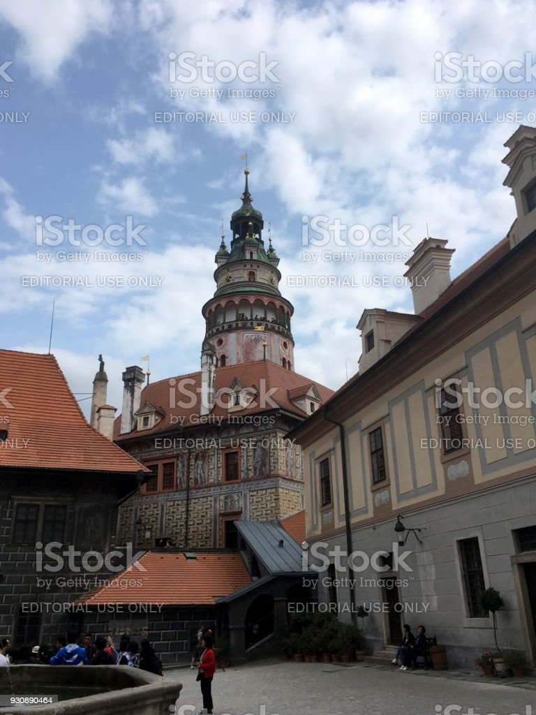 Looking up at the Iconic Castle Tower in . Renaissance Castle Tower against a blue sky and puffy white clouds. Picturesque town of Cesky Krumlov stock photo