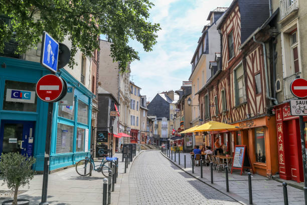 Looking up main street in Rennes, people sit in cafes and cobblestones road leads to the center of town. stock photo