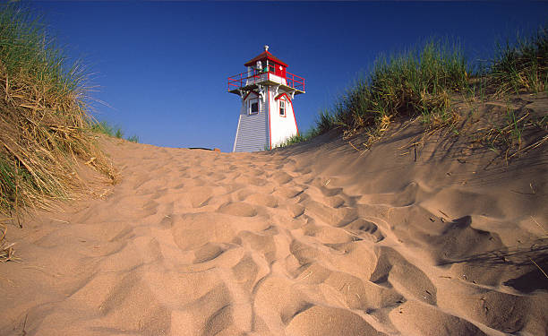 looking up sand covered hill at lighthouse - prince edward island stock photos and pictures