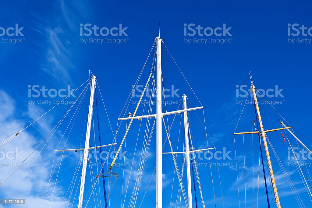 Looking up the mainmasts and blue sky background, around port. stock photo