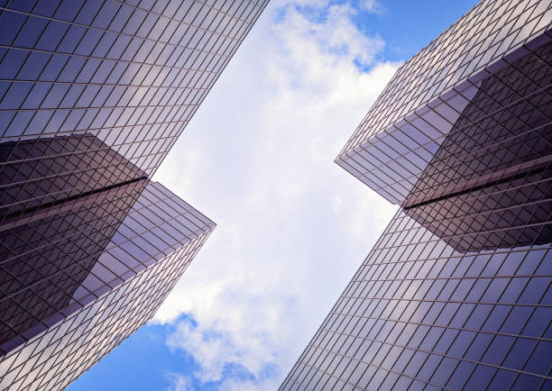 Looking up the sky between two skyscrapers. Urban symmetry stock photo