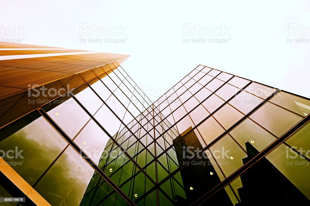 Looking up view of a modern glass building in London. Under blue sky stock photo