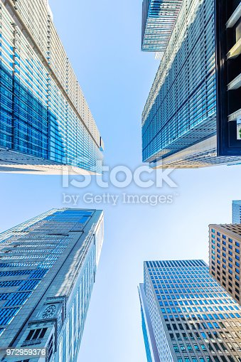 istock looking up view of panoramic modern city skyline with blue sky in tokyo, japan 972959376