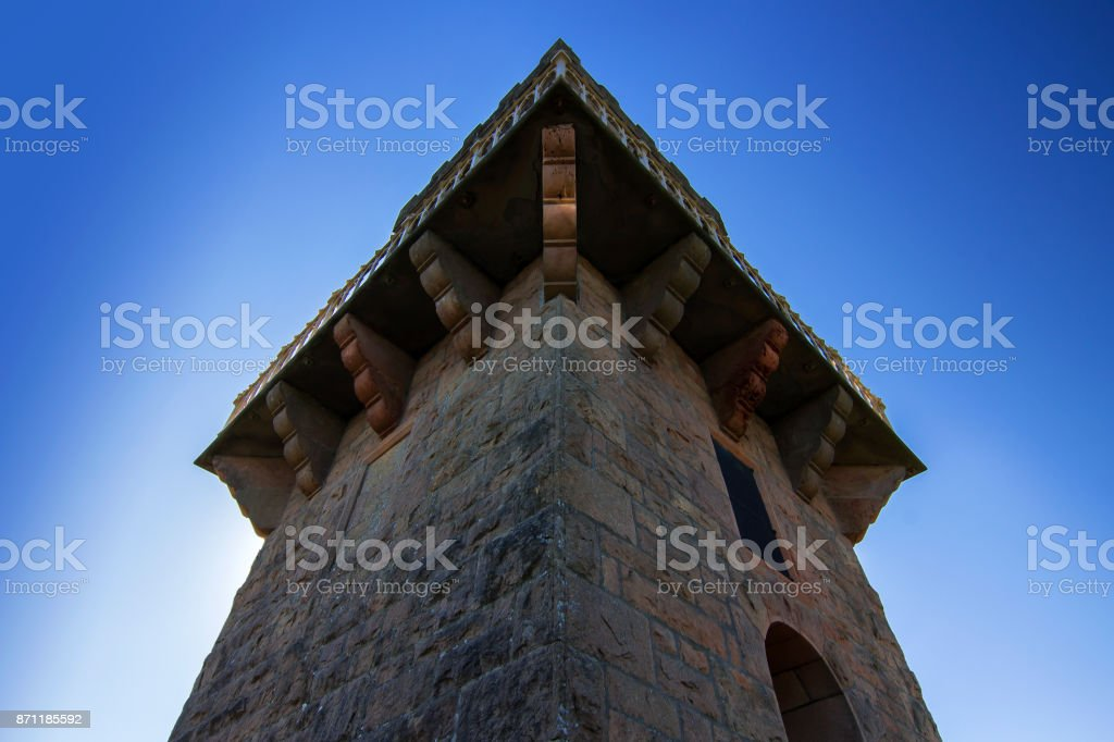 Looking upward at an old brick tower against a blue sky. Centenary Tower, Mount Gambier, South Australia, from below. stock photo