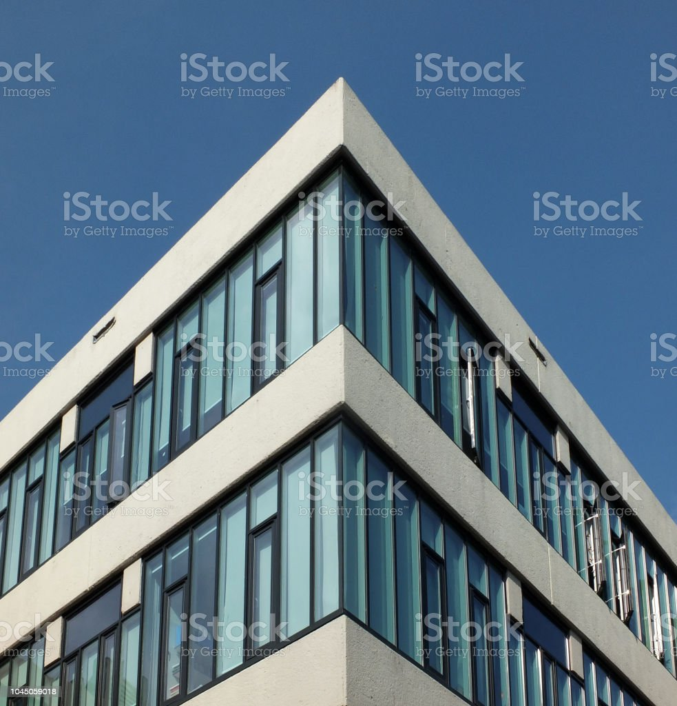 looking upwards view of a corner of a modern angular concrete high white office building with bright blue lear sky stock photo