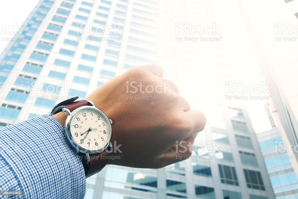 Looking watch with office building background. stock photo