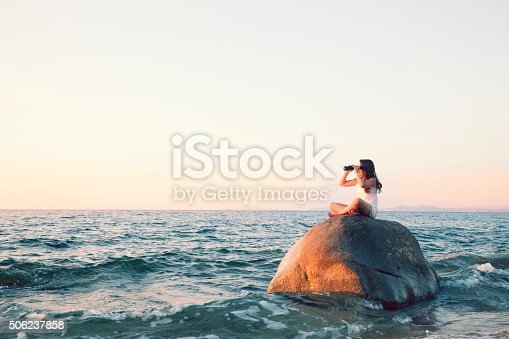 Child sitting on a boulder, in the sea, looking ahead with binoculars.
