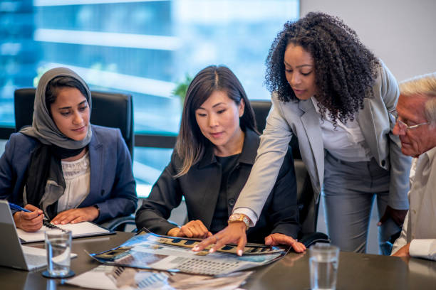 Lookinhg At Documents A group of businesspeople are having a meeting in an office. They are gathered around a table to look at documents. immigrant stock pictures, royalty-free photos & images
