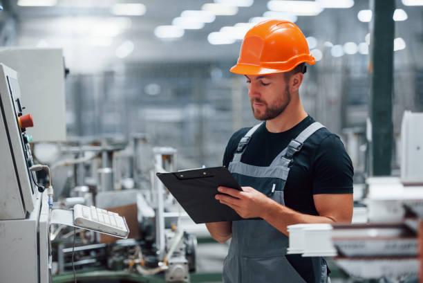 Schaut sich die Ausrüstung an und macht sich Notizen. Industriearbeiter in der Fabrik. Junger Techniker mit orangefarbenem Harthut – Foto