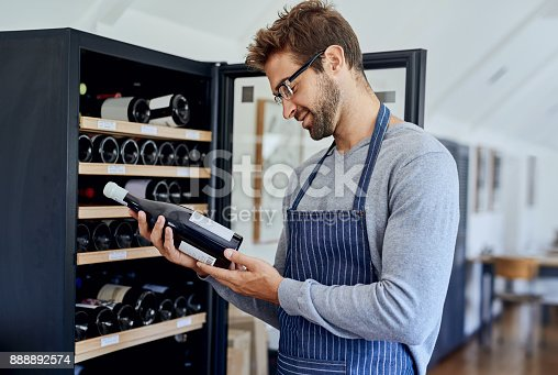 Shot of a handsome young man  choosing a bottle of wine in a restaurant