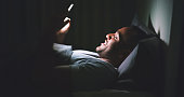 Shot of a cheerful young man using his cellphone while lying in bed late at night