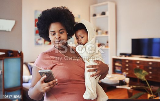 Cropped shot of a woman using her cellphone while holding her baby
