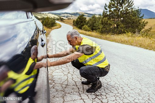 Mature man has problems with the wheel of his car. He is kneeing and looking at it with seriousness.