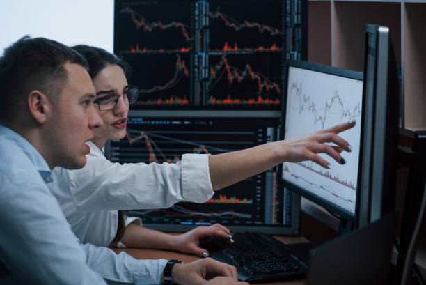 looks like we must achieve that line. team of stockbrokers are having a conversation in a office with multiple display screens - scambio commerciale foto e immagini stock