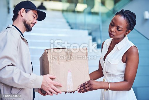 Shot of a businesswoman inspecting her delivery from the courier
