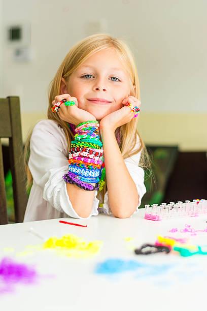 webstuhl armbändern auf ein junges mädchen hand - armband i gummi stock-fotos und bilder