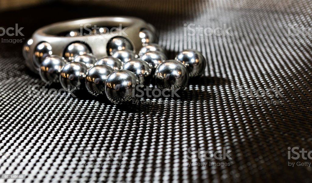 Loose ball bearings in front of an automotive wheel bearing on carbon fiber cloth. stock photo