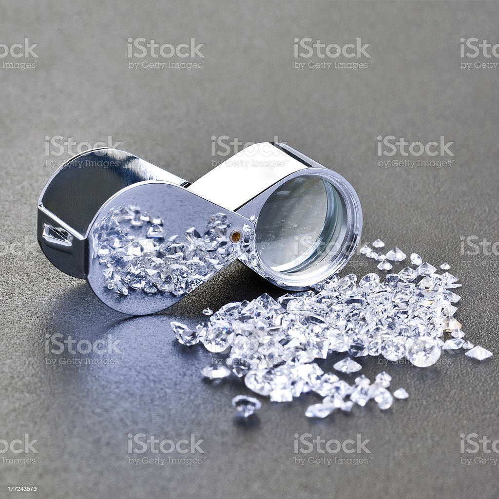 Loose diamonds next to a 10x  magnifier glass royalty-free stock photo