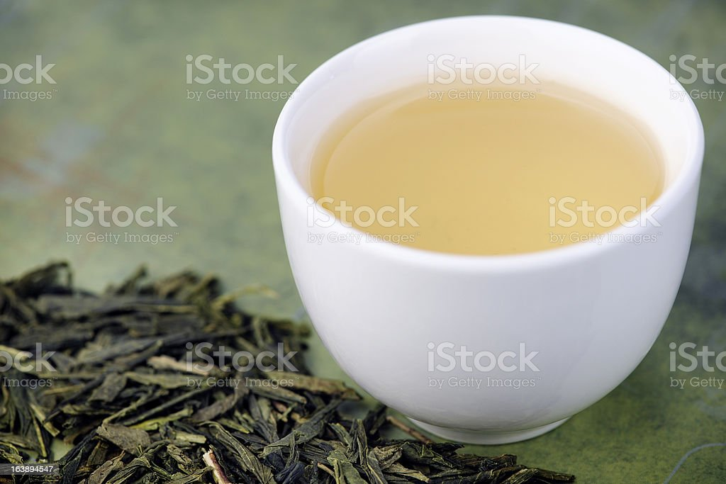 Loose green tea and cup stock photo