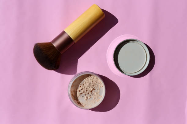 Loose Powder and Powder Brush on a Pink Surface stock photo