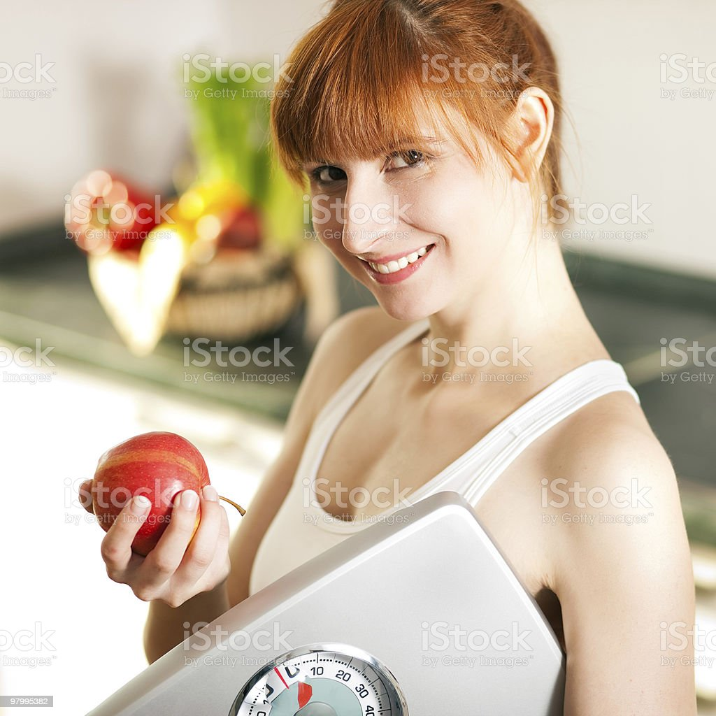 loosing weight - woman with scale and apple royalty-free stock photo