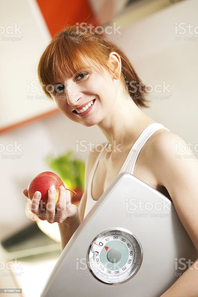 loosing weight - woman with scale and apple royalty free stockfoto