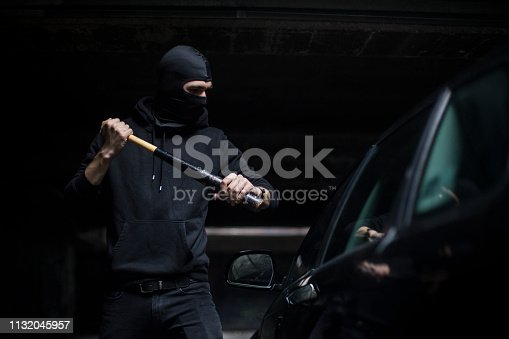 Burglar or hooligan trying to smash a car with a baseball bat. Unrecognizable Caucasian male wearing a balaclava.