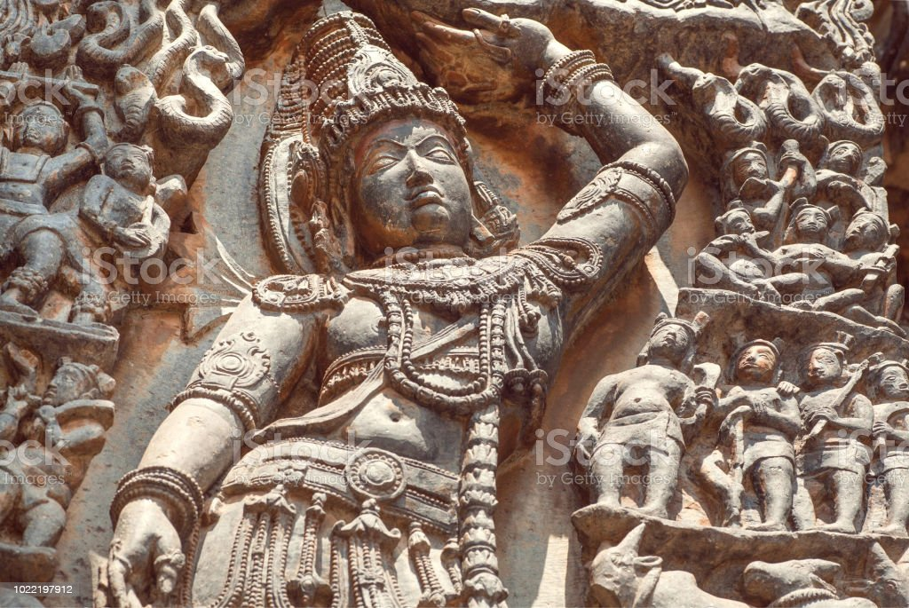 Lord Krishna with a hand raised over human, on relief of the 12th century South Indian temple. Halebidu heritage, India stock photo