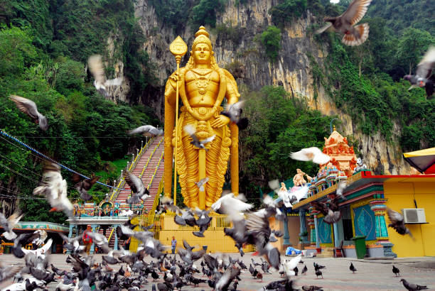 Lord Murugan Statue, Batu Caves, Selangor, Malaysia. Lord Murugan Statue is the tallest statue of a Hindu deity in Malaysia and second tallest statue of a Hindu deity in the world, only second place to the Kailashnath Mahadev Statue in Nepal.It is located at the Sri Murugan Perumal Kovil at the foot of Batu Caves. kuala lumpur batu caves stock pictures, royalty-free photos & images
