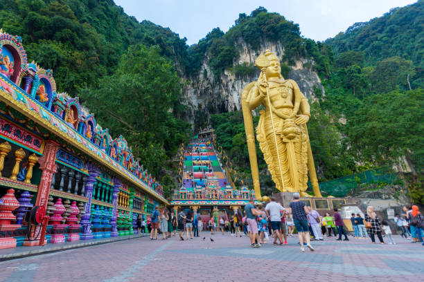 Lord Murugan statue in Batu caves. Hindu temple Square in front of Batu Caves. On the right a huge golden statue of Lord Murugan, on the left a colorful staircase leading to the temple. batu caves stock pictures, royalty-free photos & images