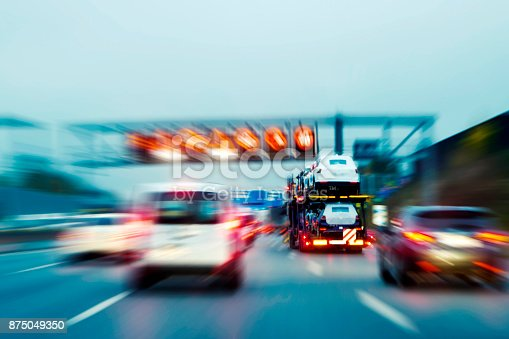 istock Lorry with new cars driving on motorway 875049350