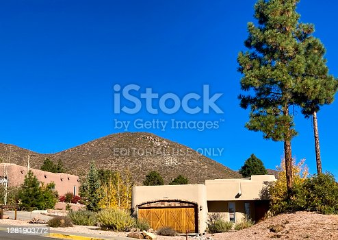 Los Alamos, NM: A residential neighborhood with adobe homes in the Los Alamos foothills, just below the line of the Cerro Grande 2000 wildfire, with burned trees visible on the hill.