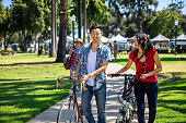 A man and woman are smiling and laughing as they walk through a park in Pasadena, CA. the stalls of a farmer's market can be seen in the background. They are pushing bicycles.