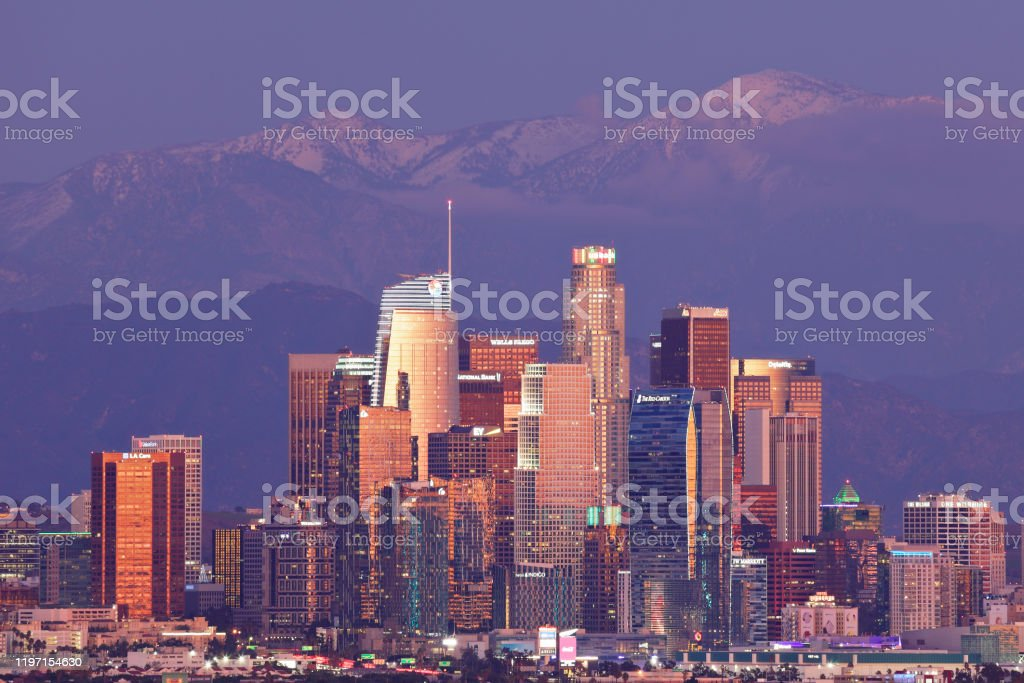 Los Angeles Skyline - Night Nighttime telephoto view of the Los Angeles skyline and the San Gabriel mountains. The modern skyscrapers of the city skyline are primarily in the financial district and the Bunker Hill  area of downtown Los Angeles. The skyscrapers are occupied by corporate offices, hotels, banks, law firms, and real estate companies. Architecture Stock Photo
