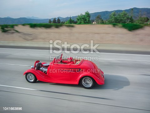 istock Los Angeles. USA. April 30, 2014. An old red car rides on the Los Angeles road. USA. 1041663896