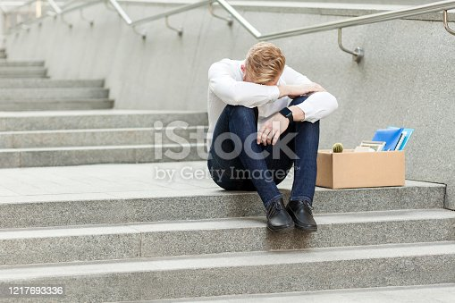 Lose job, young man lost his job, sitting on stairs holding head down, depressed, crying and don't know what to do in crisis time. feeling looser. Outdoor shot. business and health care concept.