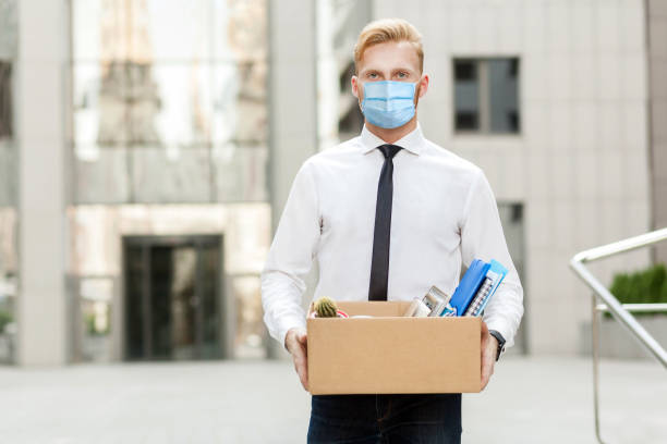 lose job, Youre fired. Unhappy business man with surgical medical mask going out with cardboard, looking at camera and feeling looser. lose job, Youre fired. Unhappy business man with surgical medical mask going out with cardboard, looking at camera and feeling looser. Outdoor shot. business, working and health care concept. downsizing unemployment stock pictures, royalty-free photos & images