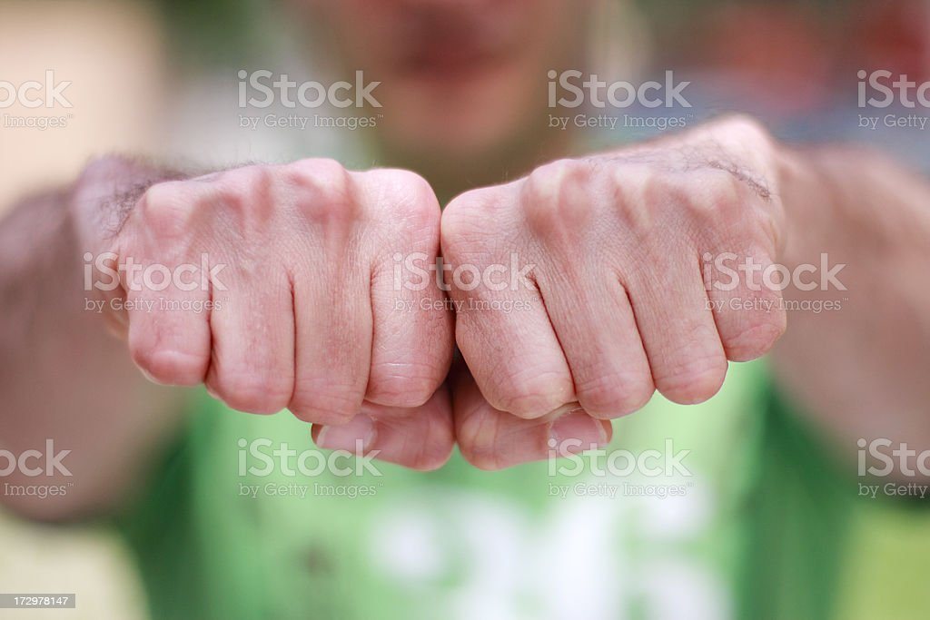 Lose of clenched fists with men in the background stock photo