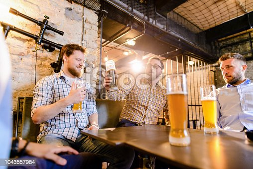 istock lose up of glass full of beer. Tree male friends sitting in a bar and drinking beer. 1043557984