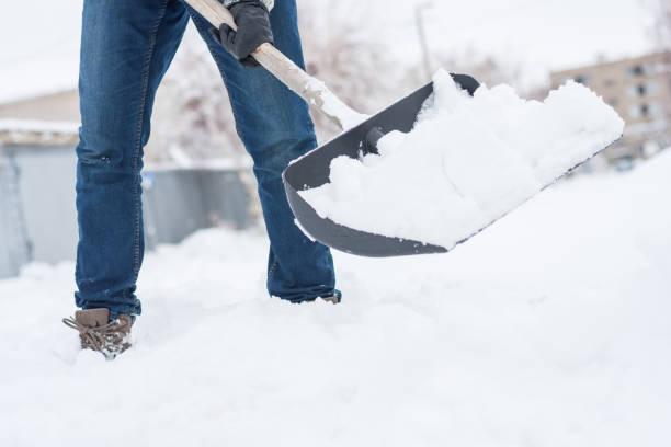 在人的手中, 失去了雪鏟的看法。在暴風雪過後, 他 hause 的後院。 - 鏟 個照片及圖片檔